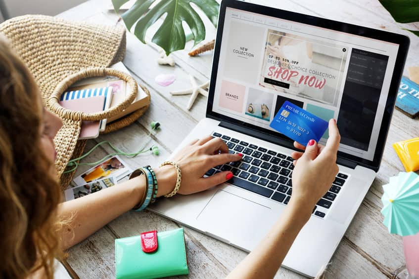 A woman online shopping with a credit card. You can avoid these pitfalls and challenges during your no spend challenge.