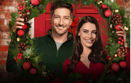 Daniel Lissing, Jessica Lowndes standing next to a christmas tree posing for the camera