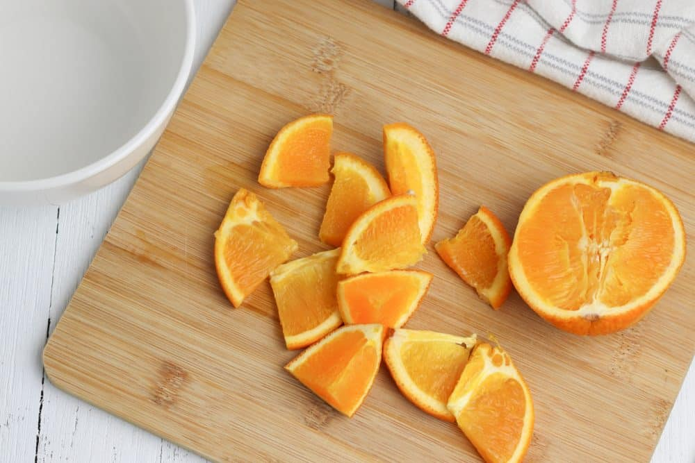 Two oranges sitting on top of a wooden cutting board, with Slow cooker and Apple