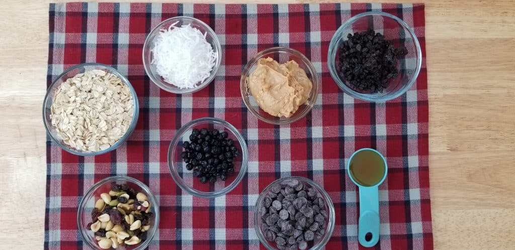 ingredients to make energy bits, chocolate chip, oats, peanut butter, coconut, raisin and nuts on a table.