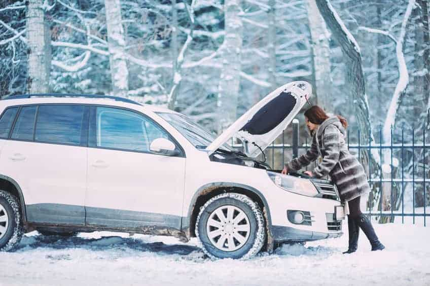 A woman stranded on the side of the road in the snow. Car Emergency Must Haves
