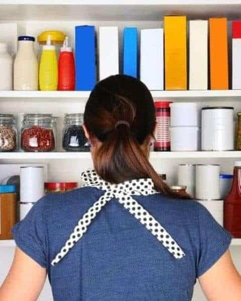 woman standing in front of an open cupboard filled with food