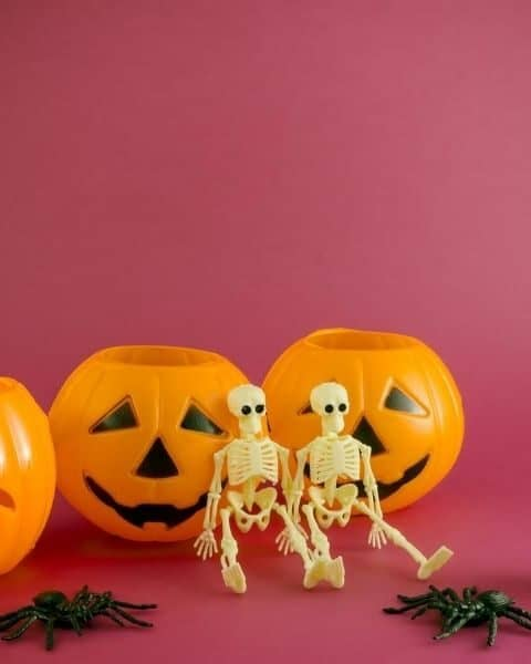 two toy skeletons sitting on a table in front of three jack o lantern pails
