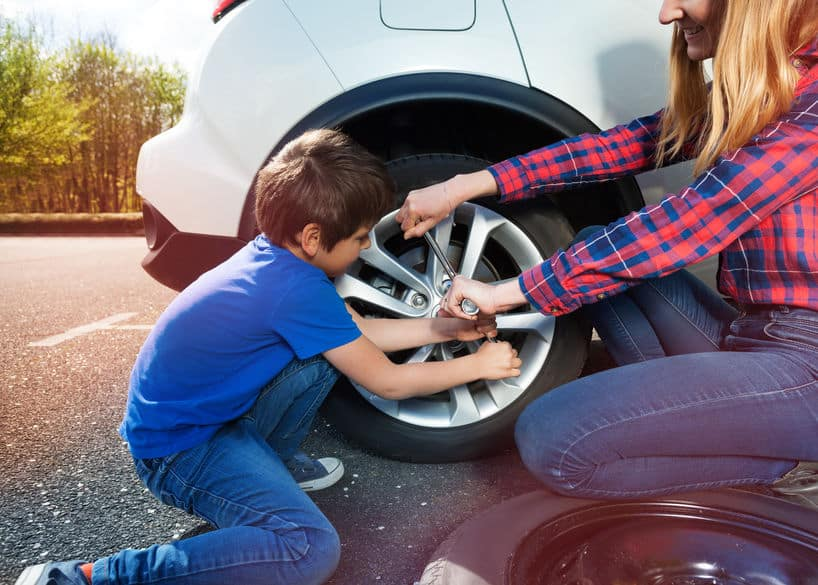 Portrait of happy little boy helping his mother to change flat tyre using lug wrench outside