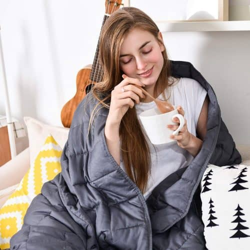 A woman sitting on a bed draped in a weighted blanket.