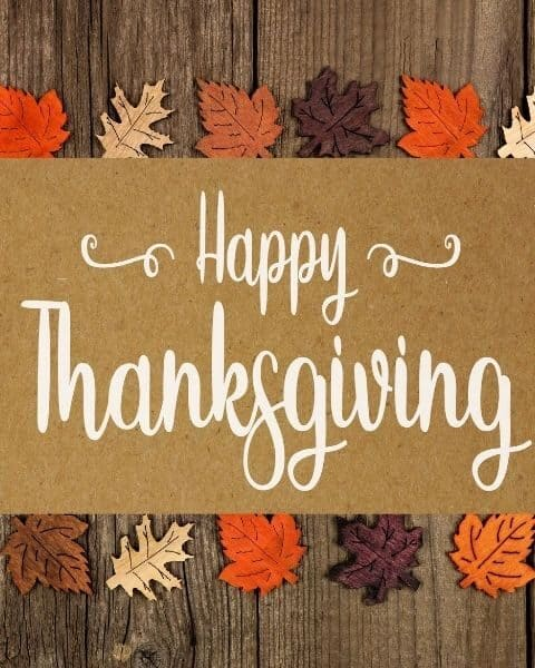 Happy Thanksgiving against a wooden background with colored leaves