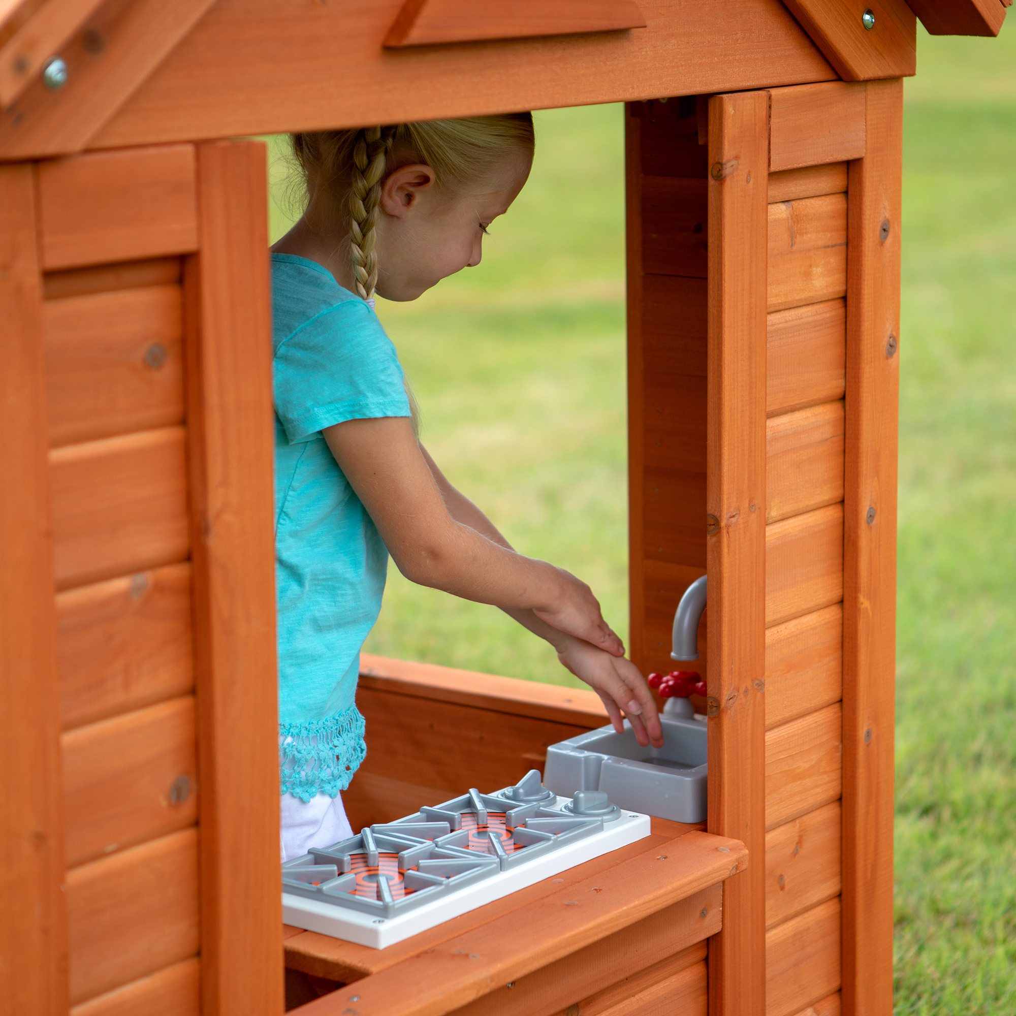 Little girl playing inside her Timberlake Cedar Wooden playhouse.
