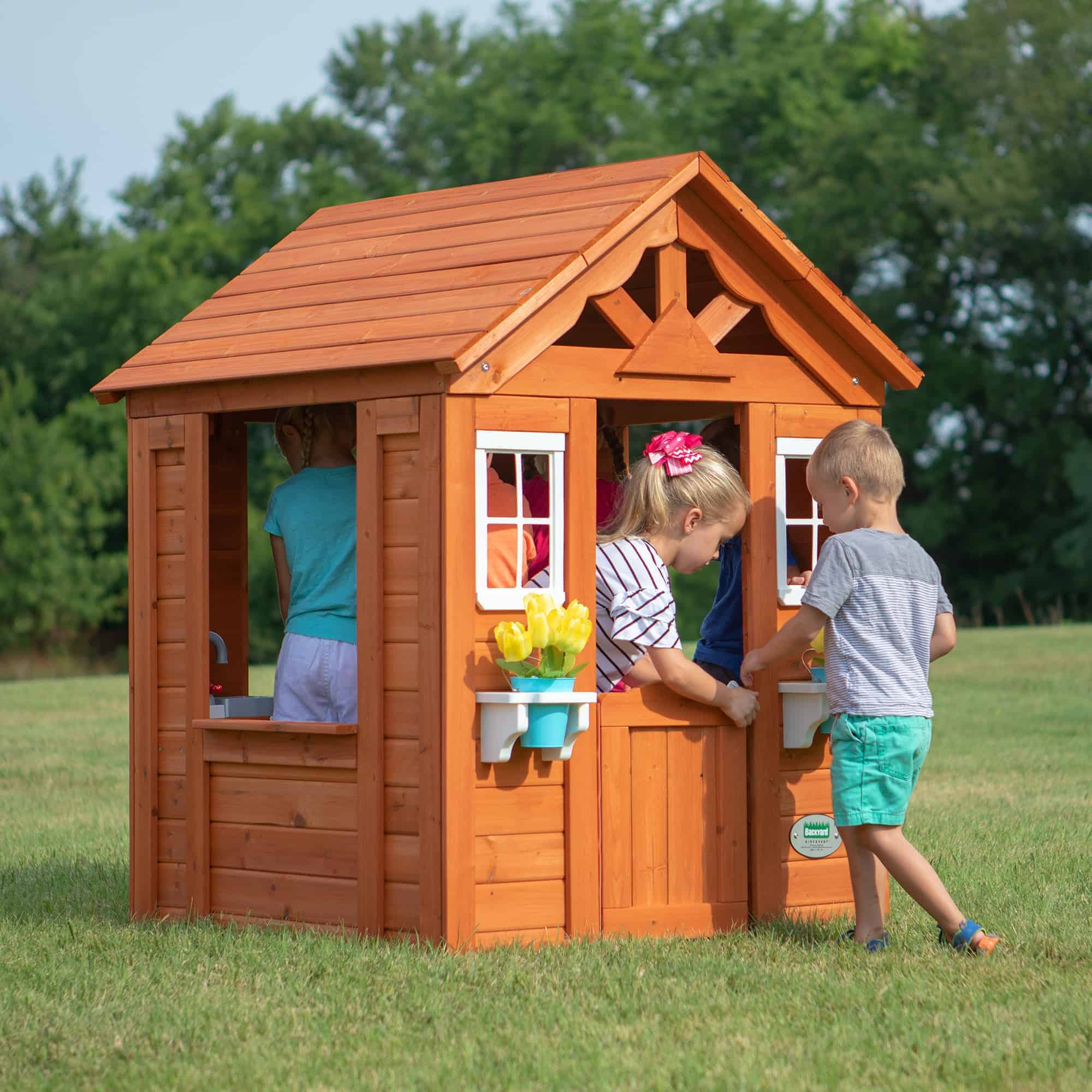 Timberlake cedar wooden playhouse with children playing together.