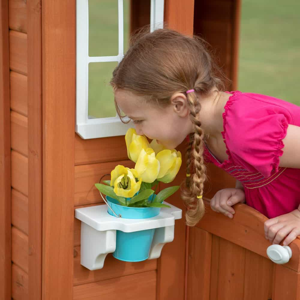 A little girl sniffing flowers from her Timberlake Cedar wooden playhouse.