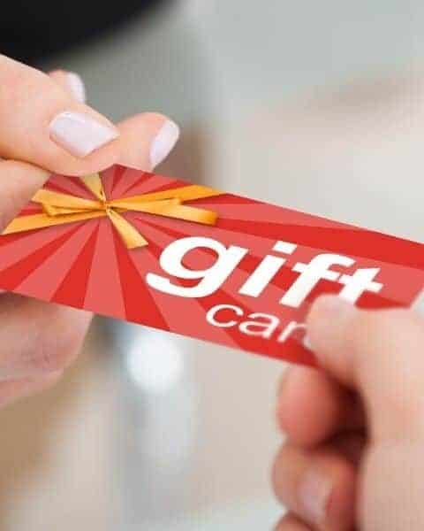 a woman giving a gift card to someone else