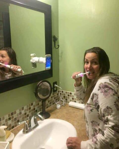 A person brushing the teeth with a rose gold Oral B 8000.