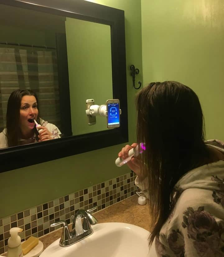 A woman brushing her teeth in front of a mirror with a rose gold Oral B 8000 toothbrush.