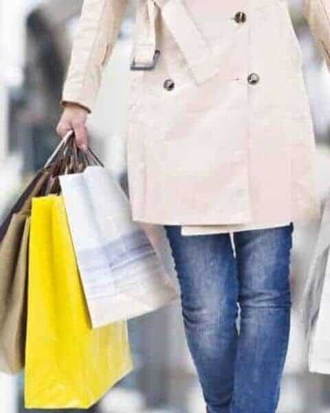 woman holiday shpping with arms full of shopping bags