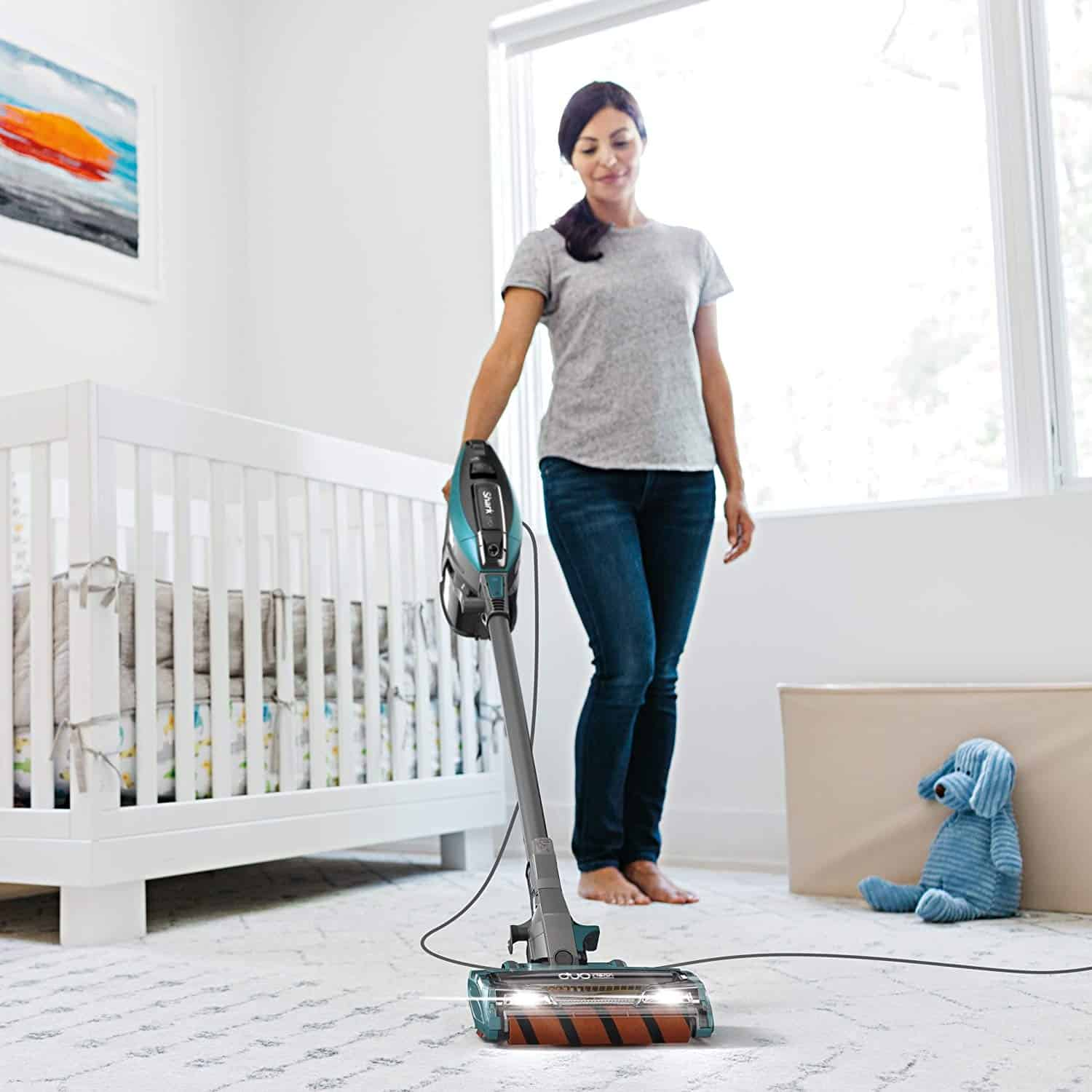 A person standing in a room, with Stick Vacuum