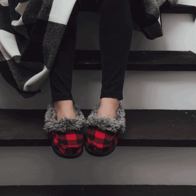 A woman sitting on the stairs wearing a pair of MUK LUKS moccasin slippers, on sale!