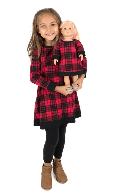 A little girl and doll in matching clothes during a Cyber Monday sale.