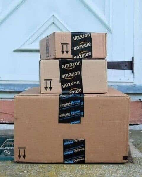 stack of amazon packages on a front porch