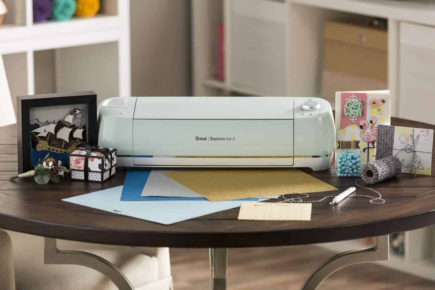 Cricut Explore Air on a crafting table surrounded by supplies.