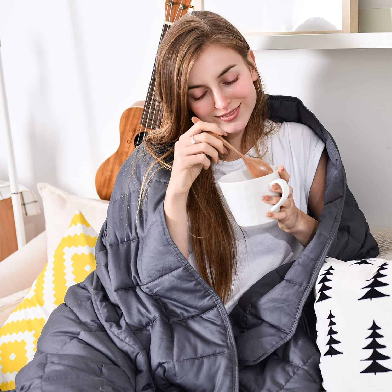 woman eating out of a bowl wrapped in a blanket