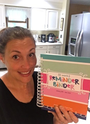 A woman smiling with her Power Planner Reminder Binder.