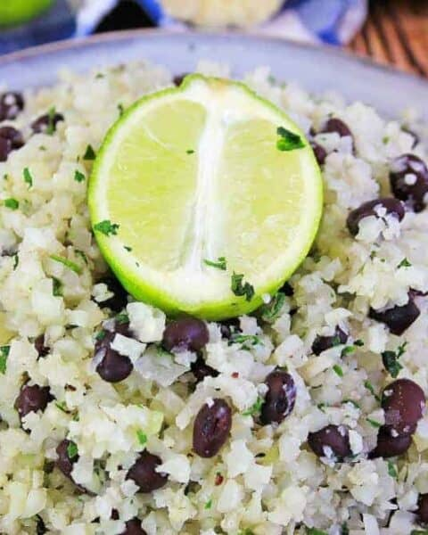 A close up of a plate of food with rice and vegetables, with Cauliflower and Lime
