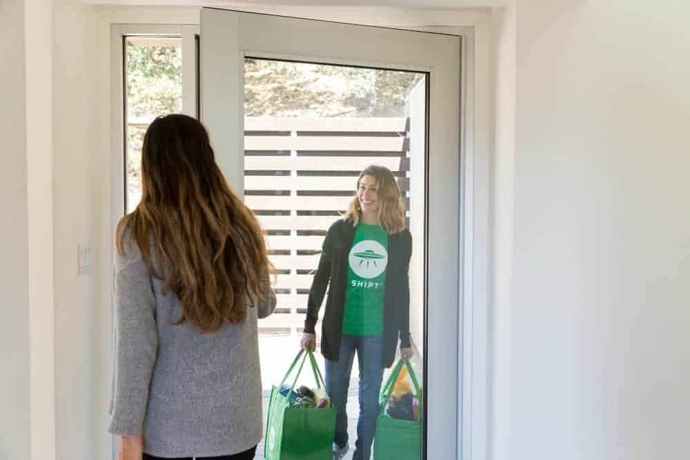 A woman answering the door to her Shipt shopper holding two bags full of groceries.
