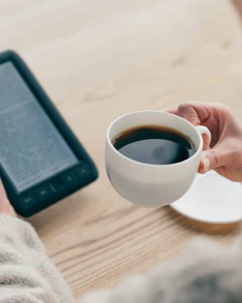 A woman drinking a cup of coffee while reading from her Kindle unlimited.