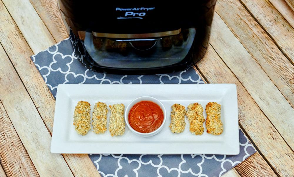 mozzarella cheese sticks on a plate with pizza sauce in front of an Air Fryer