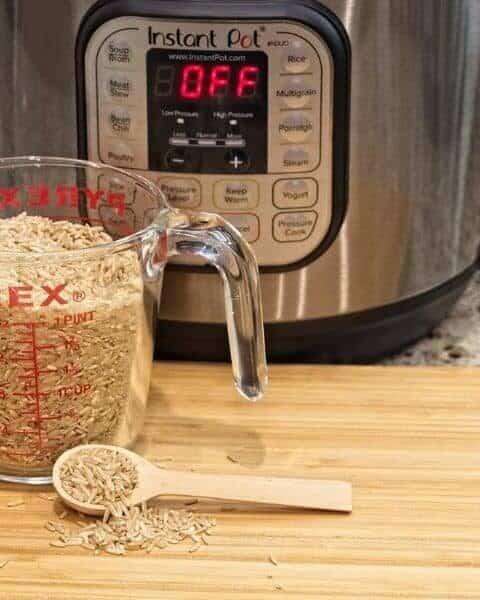 instant pot with a measuring cup of rice on a table