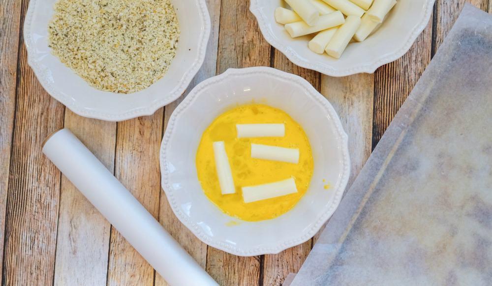 mozzarella cheese sticks in a bowl of beaten eggs