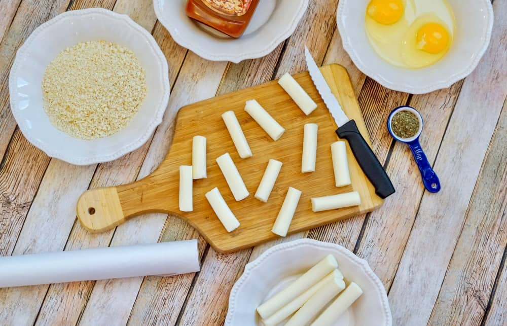 mozzarella cheese sticks cut up on a cutting board with a knife and cheese stick ingredients