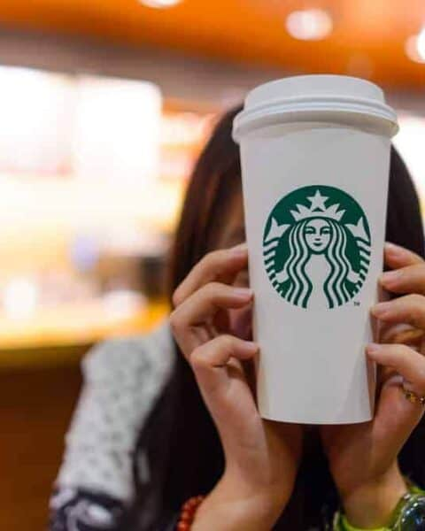 A person holding a Starbucks logo coffee cup.