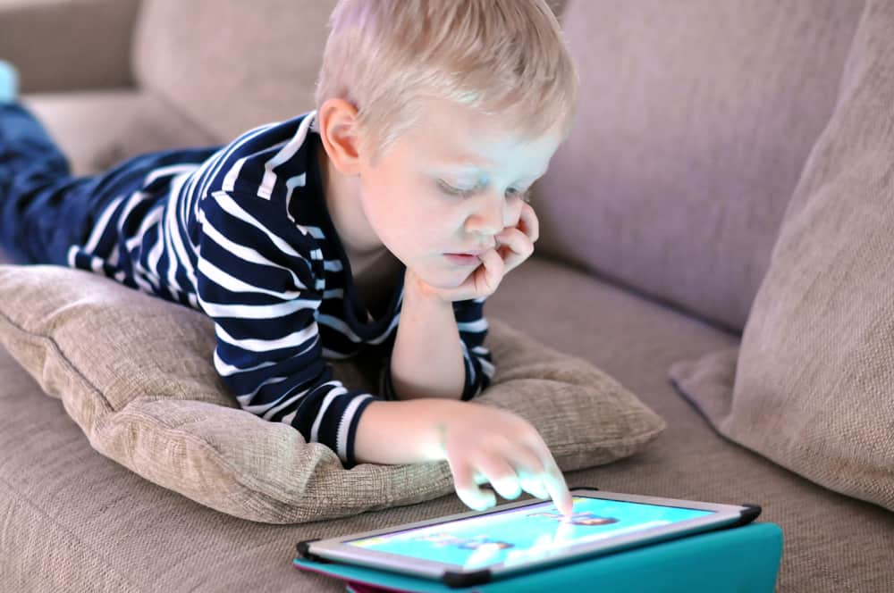 Boy reading and playing on tablet for educational purposes.