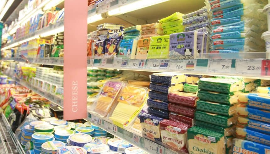 A customer shopping for cheese and other dairy products at a supermarket