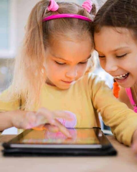 Two beautiful little sisters sit at a table and play on a Tablet PC.