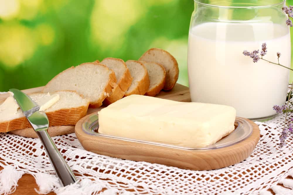 Butter on wooden holder surrounded by bread and milk on natural background
