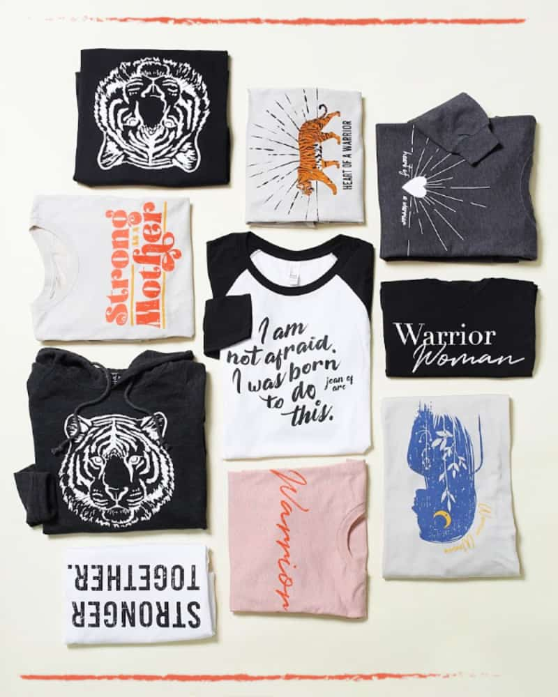 Close ups of a variety of t-shirts from the Warrior Women clothing line collection.