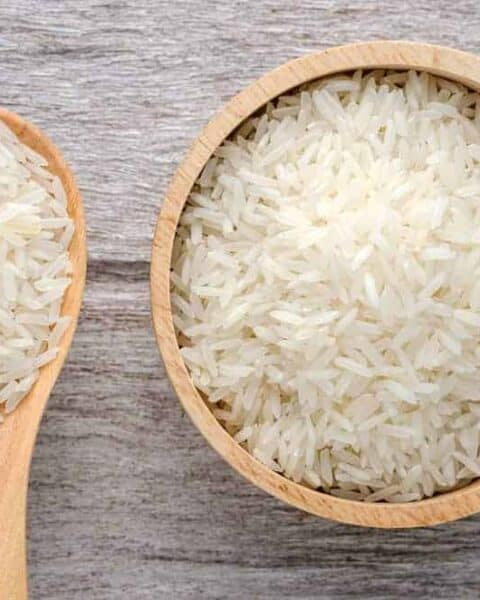Uncooked rice in bowl on white wood background