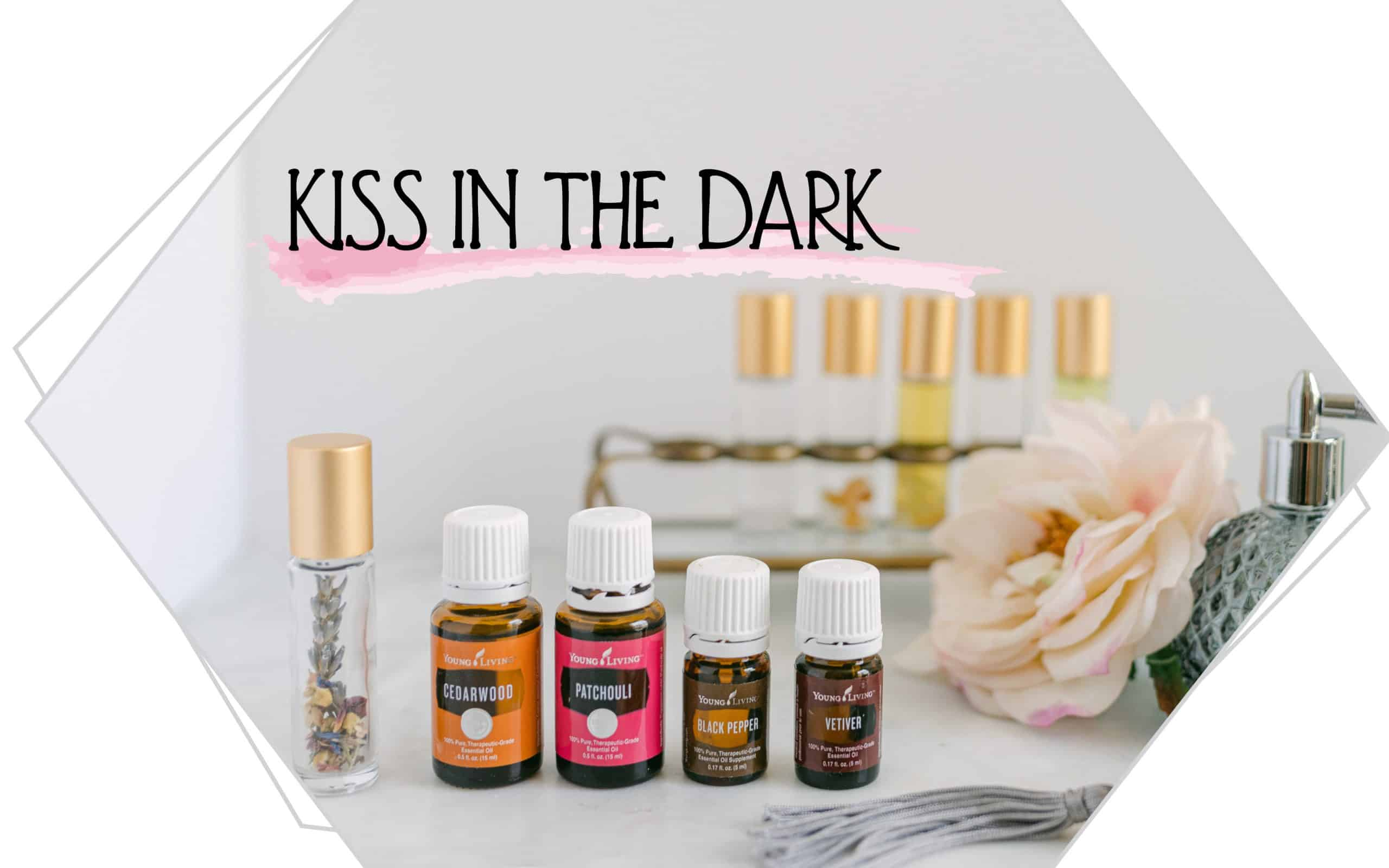 Kiss the Dark written on a background with essential oil and roller bottles.