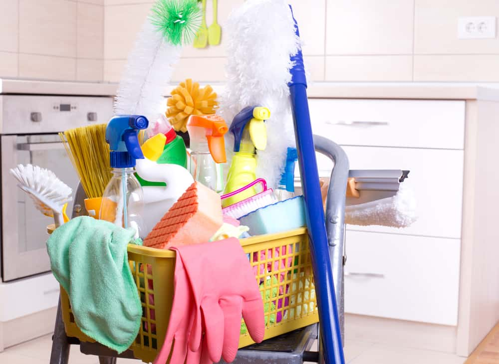 Cleaning supplies in plastic basket on ladder and mop in the kitchen