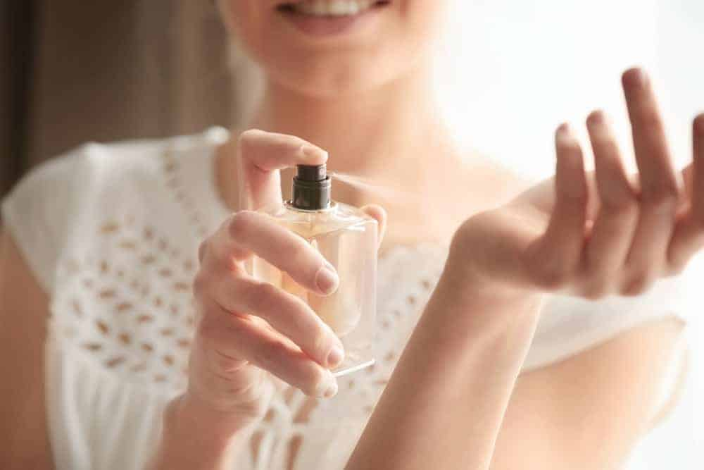 Beautiful young woman with bottle of perfume at home.