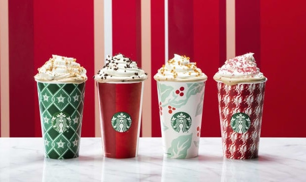 A variety of Christmas drinks in Starbucks cups with whip cream and toppings.