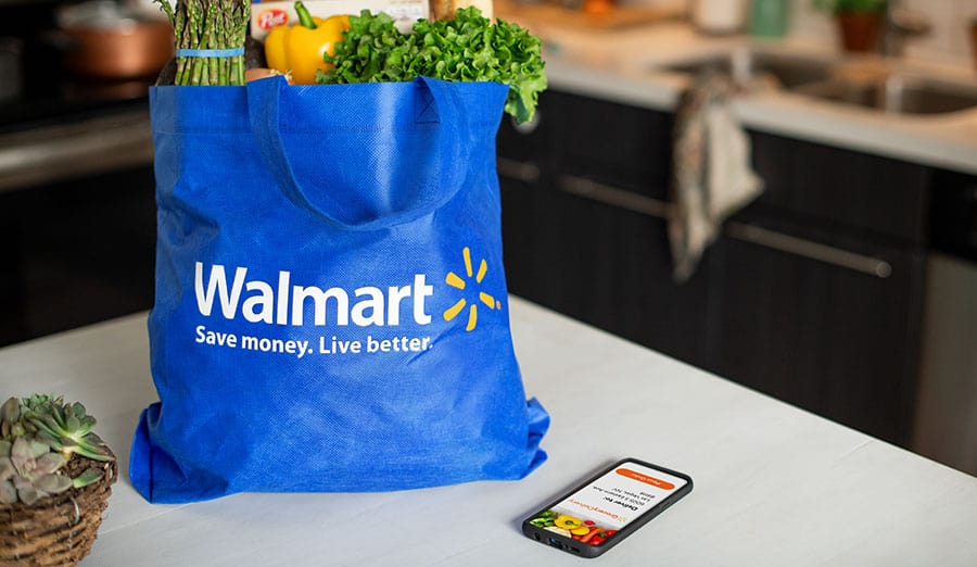 Walmart bag on a counter filled with groceries sitting next to a cell phone