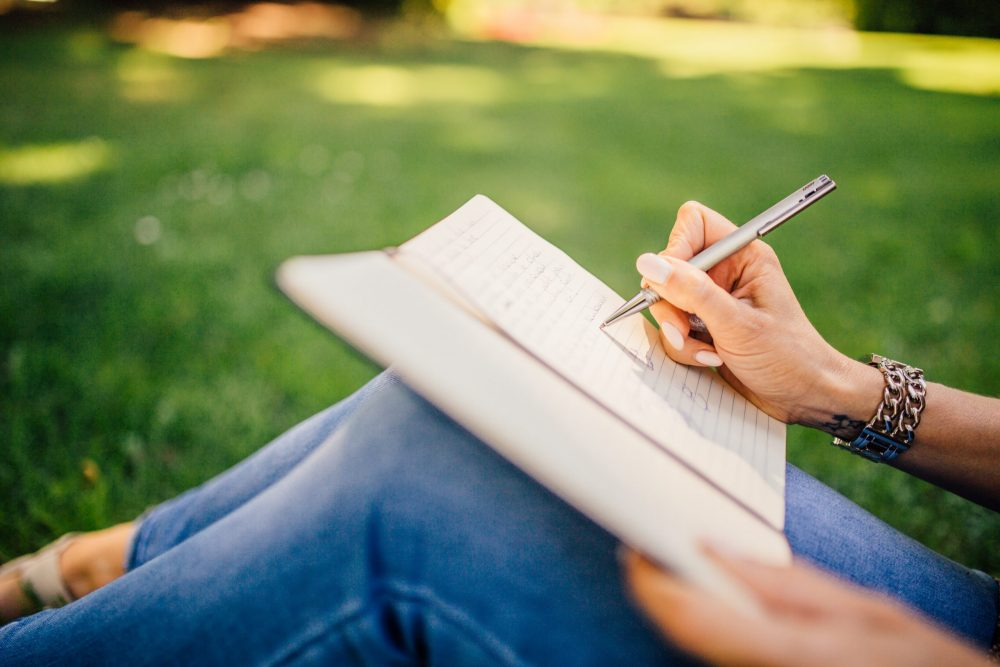 A person sitting on the grass writing in her journal.