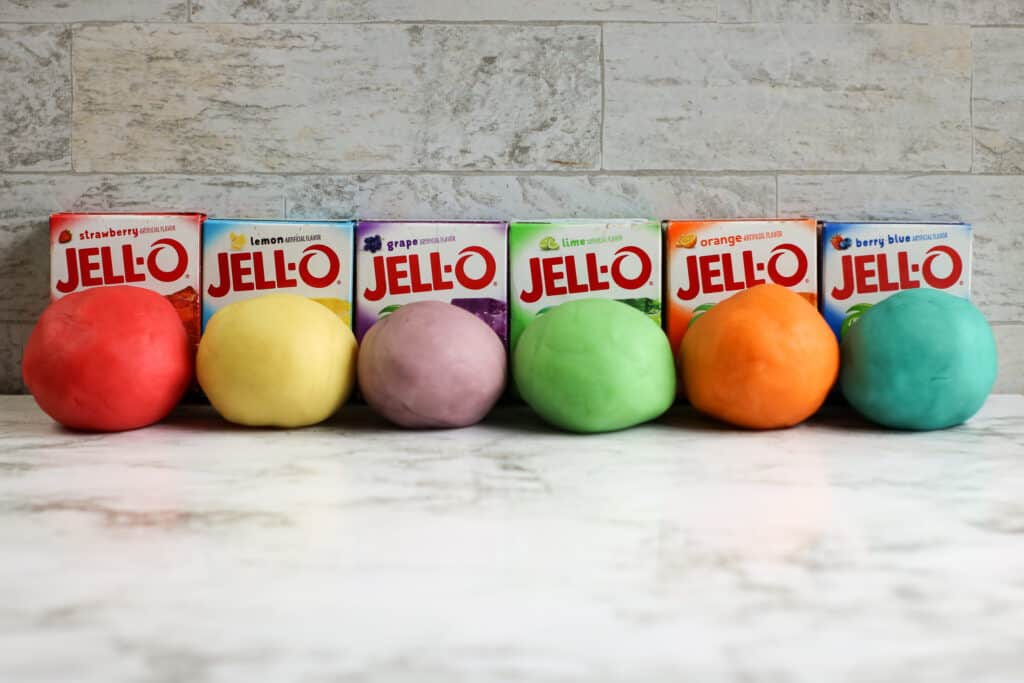 several balls of colored playdough lined up on a table with boxes of Jello