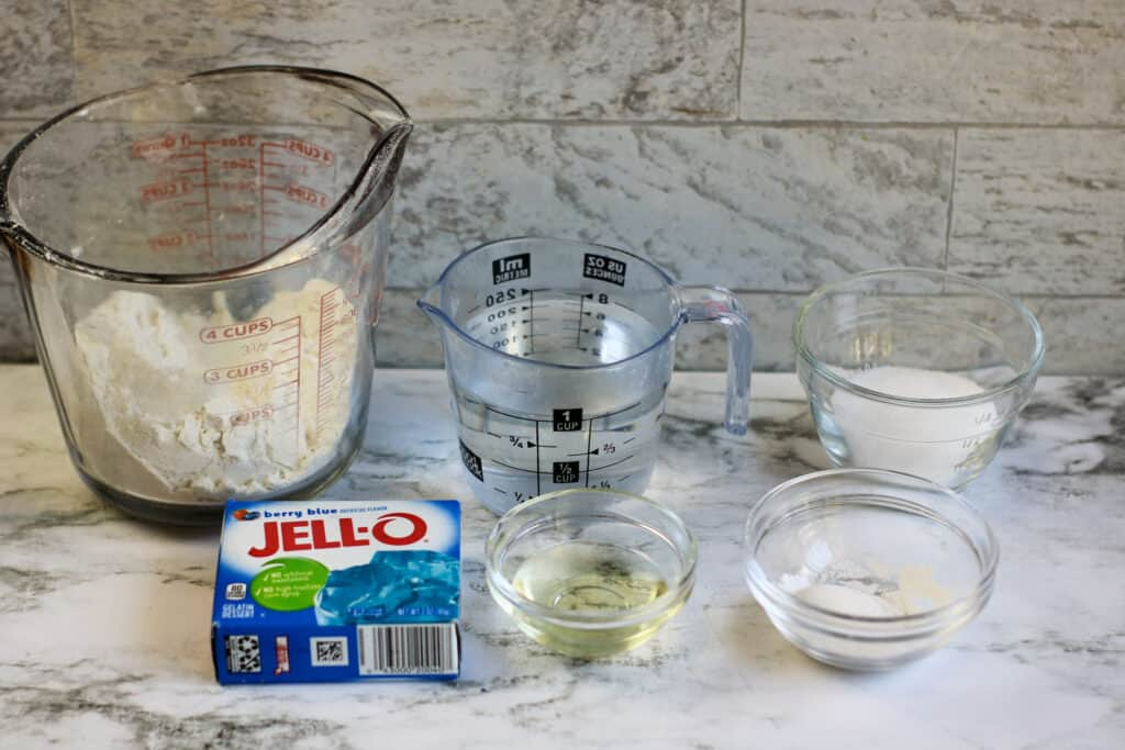 Measuring cups and bowls sitting on a counter filled with ingredients to make Jello Playdough
