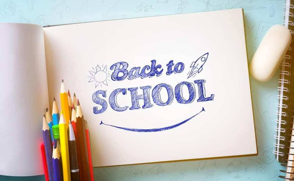 """A notebook with a drawing of a rocket ship and the words, """"Back to school"""" colored inside."""