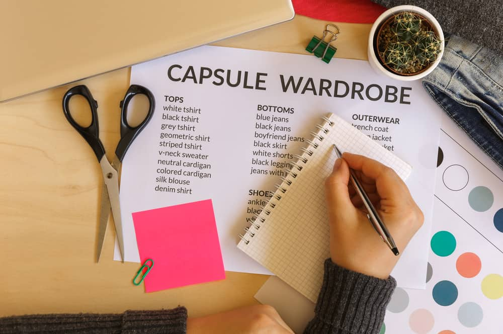 Woman creating a capsule wardrobe: fashion, minimalist and technology concept. Flat lay