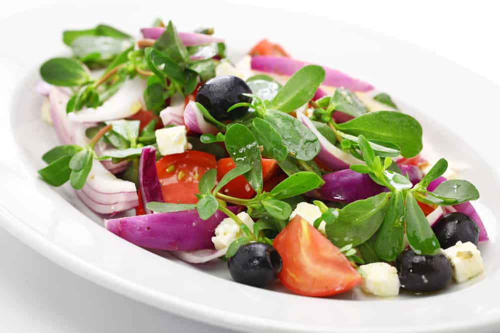 Greek Salad on a white plate with purslane clippings added.