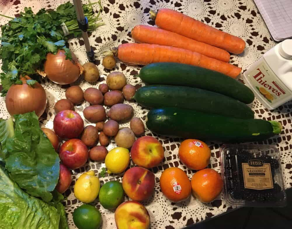 carrots, cucumber, oranges, apples, potatoes, lettuce, onions, lemons, limes and berries sitting on a kitchen table
